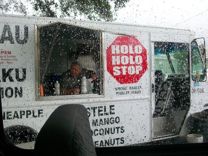 Food truck full of authentic Hawaiian food alongside rainy road near the North Shore of Oahu.