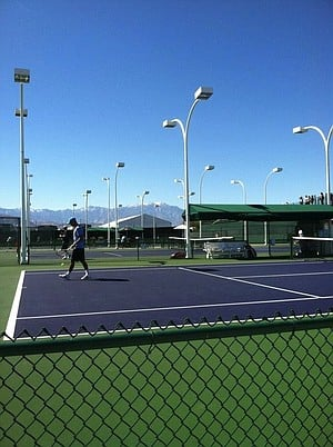 Indian Wells practice courts, snowcapped San Jacinto Mountains in the background.