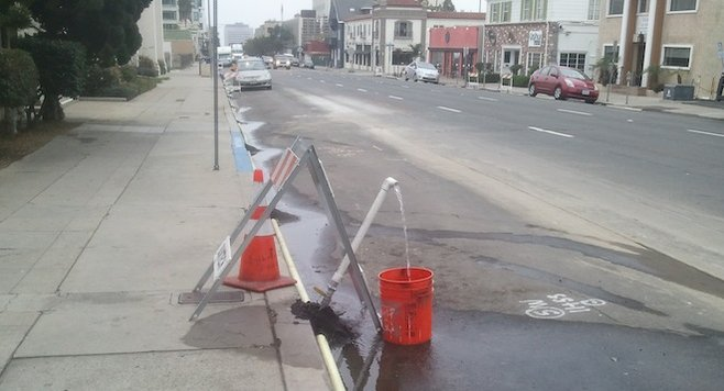 Water fills a bucket on Fifth Avenue — presumably for testing