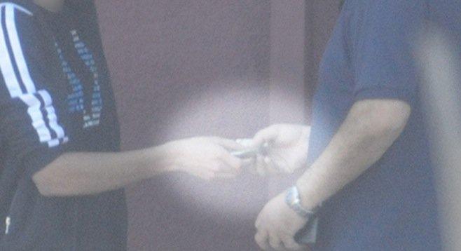 FBI surveillance video shows a DMV employee accepting cash from a license applicant