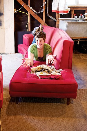 Molly Whittakar at her upholstery workshop, on a customer's couch that she will rebuild.