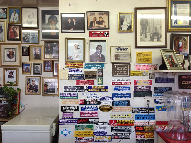"""Behind the counter at Sister Pee Wee's is a mix of memorial photos and kitschy bumper stickers, including one that says """"Hire a teenager while they still know it all."""""""