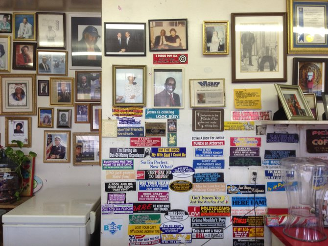 "Behind the counter at Sister Pee Wee's is a mix of memorial photos and kitschy bumper stickers, including one that says ""Hire a teenager while they still know it all."""