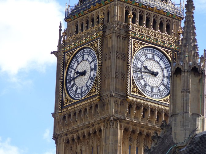 A picture capturing the beautiful, ornate decorations on the Big Ben in London, England.