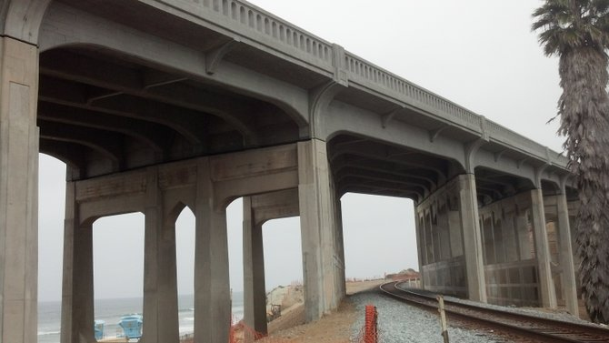 Newly-retrofitted bridge supports, a railroad, and a coastline