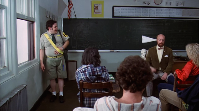 The old paper-airplane-in-the-ear gag. Paul Bartel in Rock 'N' Roll High School.