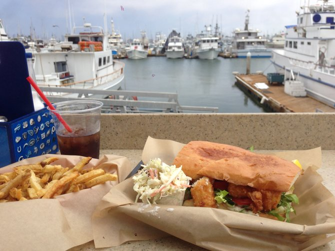 Tasty sandwich, fries and boats. Beer battered fish sandwich. Mitch's Seafood.