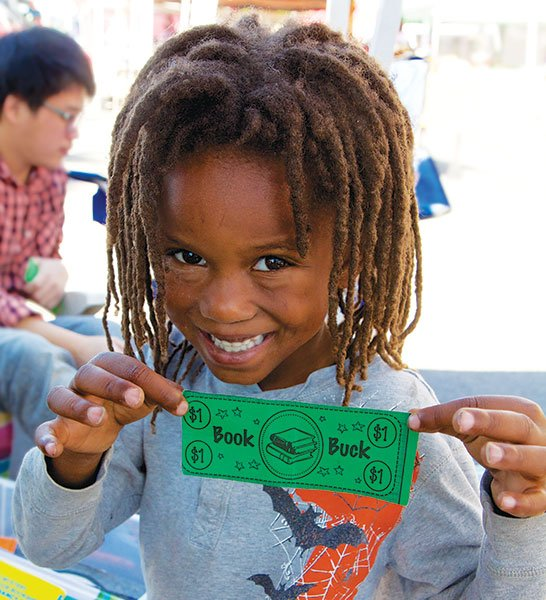 """A young reader shows off a """"Book Buck"""" reward for reading a book. Book Bucks can be traded for prizes."""