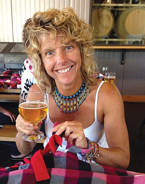 Kim Bolivar, founder of Random Acts of Kindness San Diego, sips beer and makes blankets for cancer patients at a fund raiser hosted by Societe Brewery.
