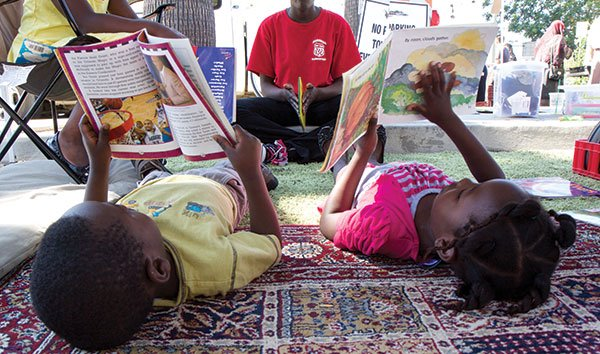 """Kids read for """"Book Bucks"""" in the Story Tent at the City Heights Farmers' Market."""