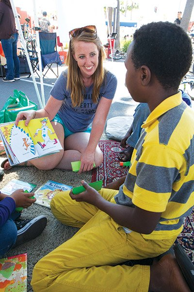 Emily Moberly offers a book to a young reader at her Story Tent in the City Heights farmer's market.