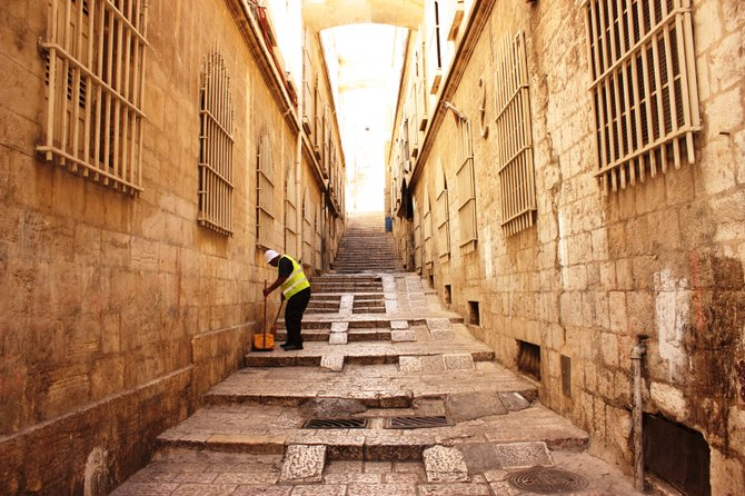 "A man sweeps trash off the street in Jerusalem's historic ""Old City."""