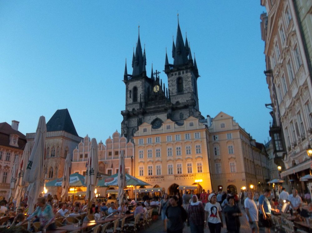 Týn Church rises up behind Old Town Square at dusk.