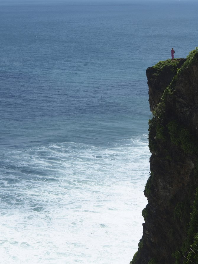 Perched on a cliff, overlooking the Indian Ocean and Uluwatu Temple in Bali.