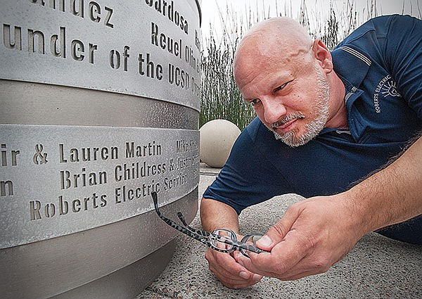 Mat Wahlstrom points to his business's name on the base of the Pride flag monument.