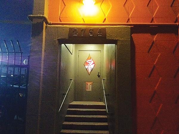 Barred, diamond-shaped peep-window in the door...speakeasy?