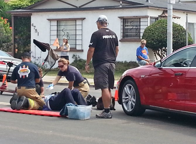 Paramedics stabilize accident victim for transport to hospital