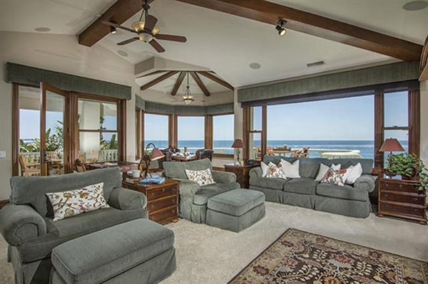 Vaulted ceilings and custom beams are in the living room, family room, and dining areas.