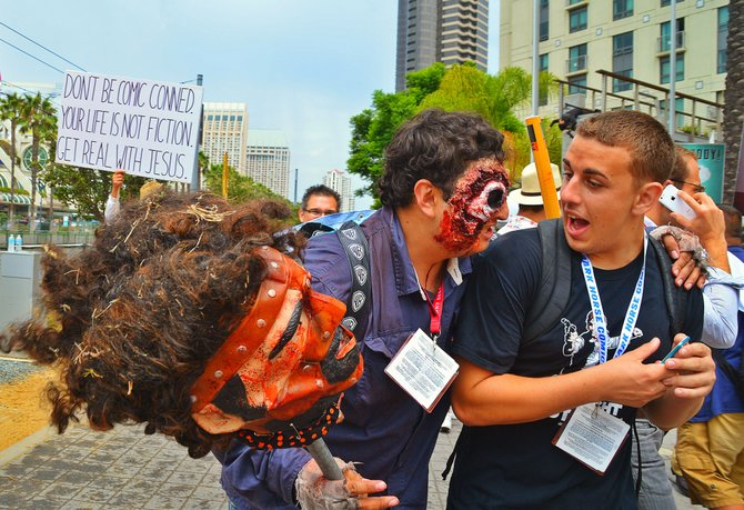 A costumed Comic Con attendee sneaks up his friend.
