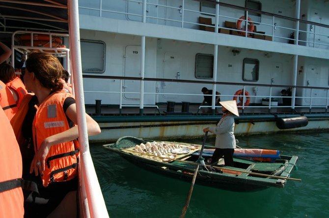 Peddler wearing nón lá (leaf hat) sells her wares on a sampan to the ship's passengers.