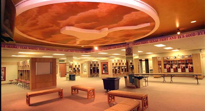 University of Texas locker room, where the team is valued at $139 million and coach's salary is $5 million