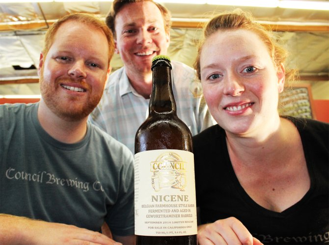 Council's Jeff Crane (background), Curtis and Liz Chism pose with a bottle of their first barrel-aged beer, Nicene  - Image by @sdbeernews