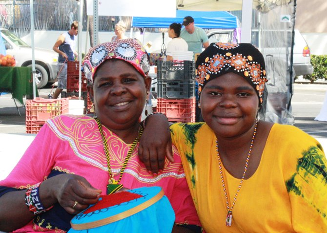 Khadija Musame and Madina Mah take a break from their produce stand to pose for a photo