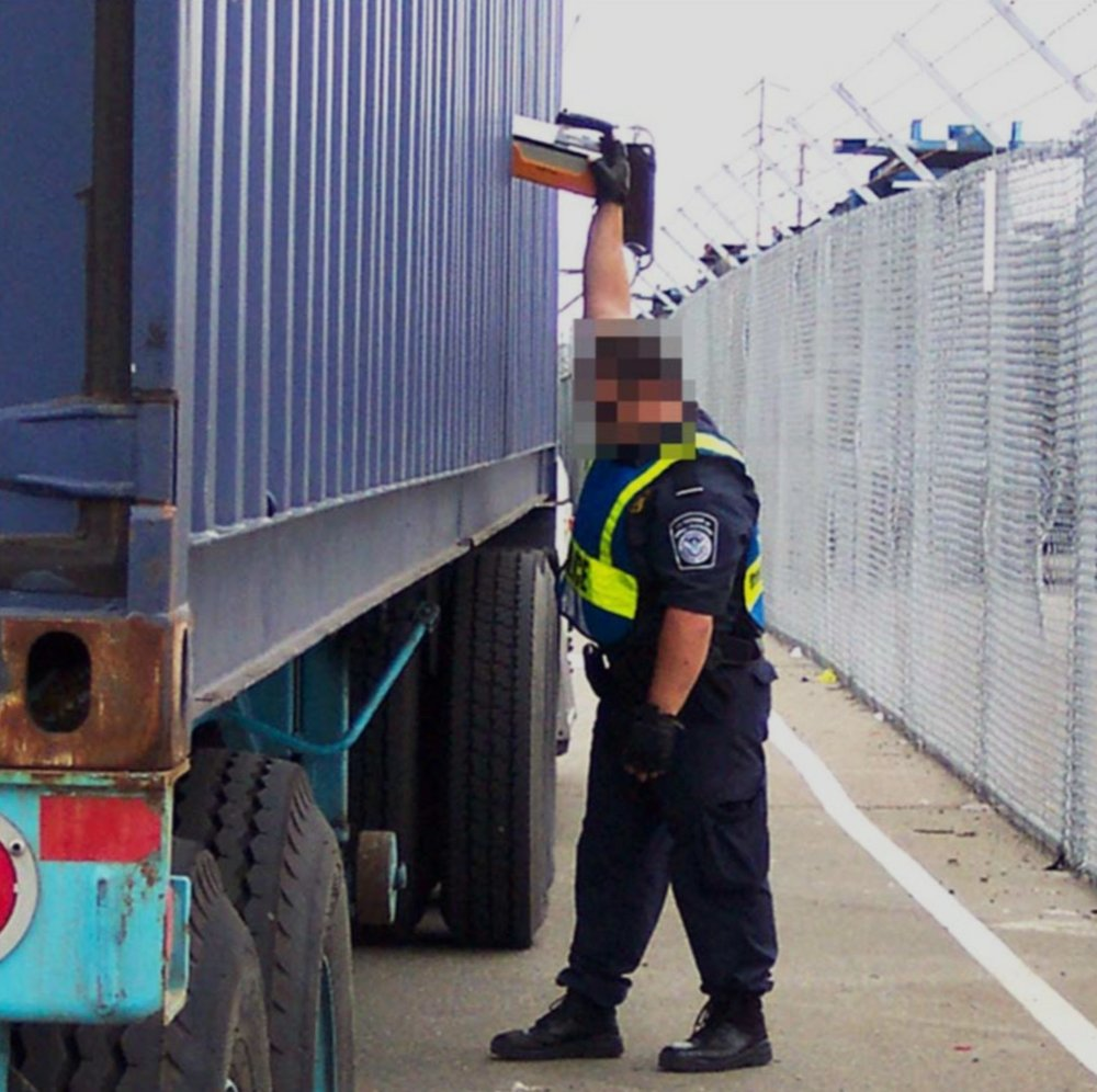 CBP agent checking shipping container with radio isotope identification device