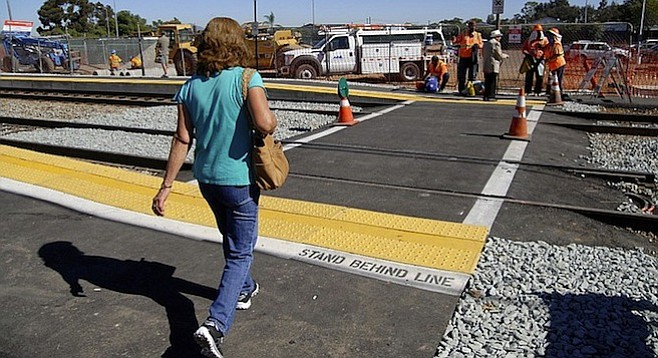 Commuter crossing the tracks at the Palm Avenue trolley station on November 8