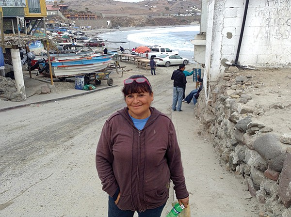 Saritha coming up from where the boats haul up on the cove's beach