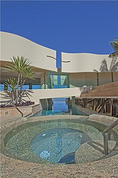 The pool passes under the house to another entertainment area.