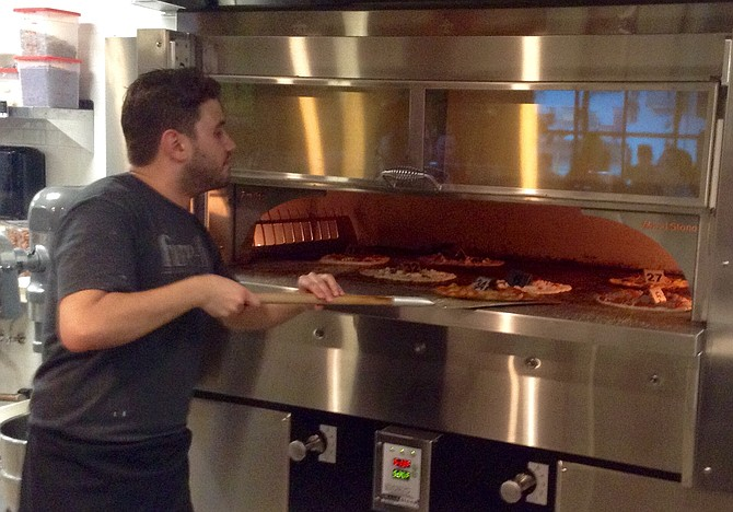 George manages quick-bake pizzas in 550-degree oven