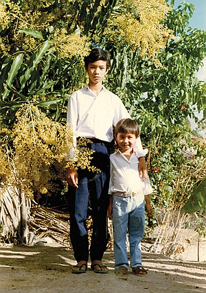 Tam with his older brother in their village. After my brother died, my mom received offers from people offering their children to pretend to be him so that their child can come to America with us.