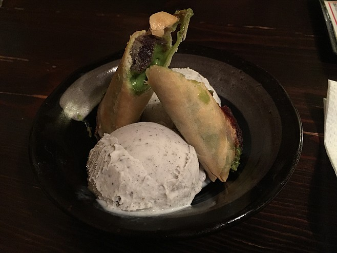 Black sesame ice cream with green tea and red bean spring rolls, earthy-sweet.