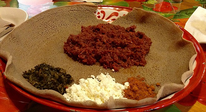 Kitfo — steak tartare, Ethiopian-style —with its flavorings on top of the injera