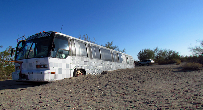 A half-buried bus named Walter greets visitors to East Jesus, a self-sustaining art community in the Southern California desert.
