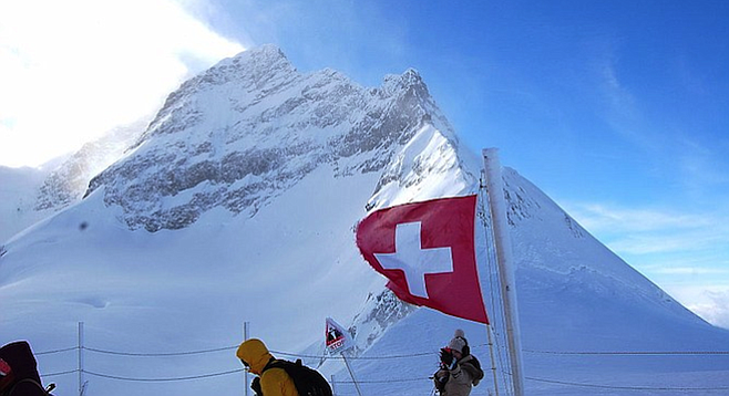 The wind-whipped Swiss flag, and tourists, at the Jungfrau's Plateau vantage point.