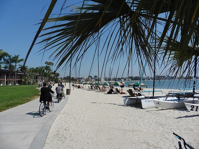 Cyclists pedal past Catamaran Resort on Bay Front Walk in Pacific Beach.