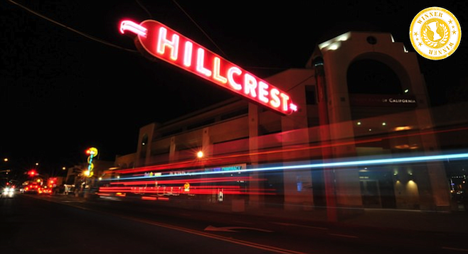 The iconic Hillcrest sign glows above University Ave. traffic at night.  (Reader stock)
