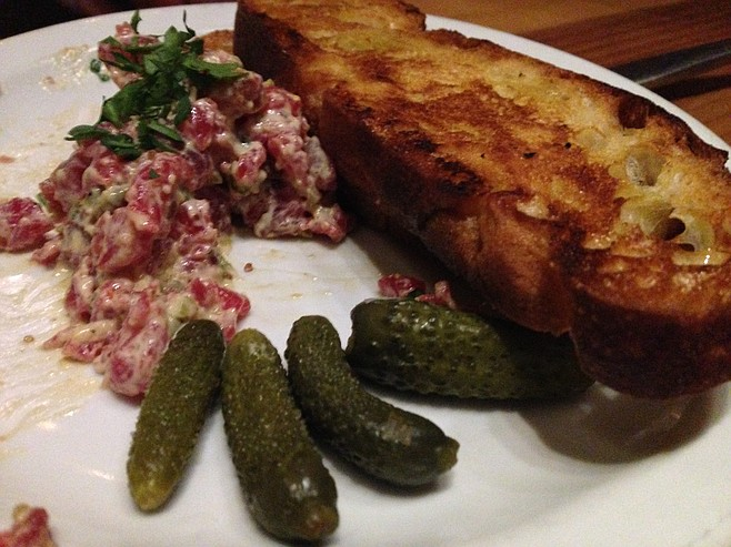 Making a dent in the steak tartare while the cornichons go relatively unnoticed.
