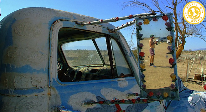 Man in the mirror at Salvation Mountain.