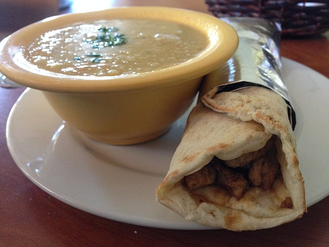 A bowl of dry soup and a tasty chicken shawerma wrap