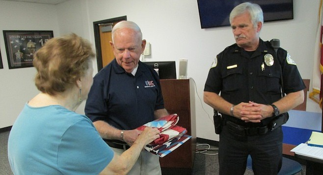 Nancy Connor donates her damaged flag (returned by Lt. Leonard Cosby) to Chuck Atkinson of the Veterans Assn. of North County, to be properly retired.