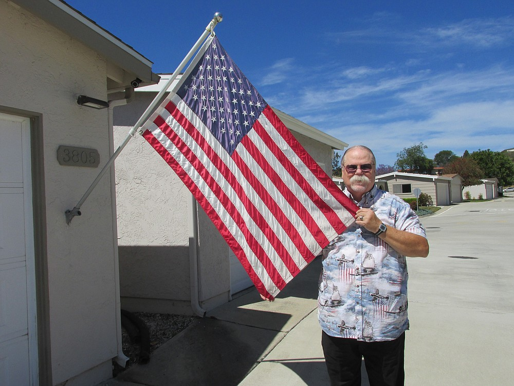 Oceanside's Michael Rank shows off his replacement flag. The security camera mounted above the flagpole helped police find the vandals.