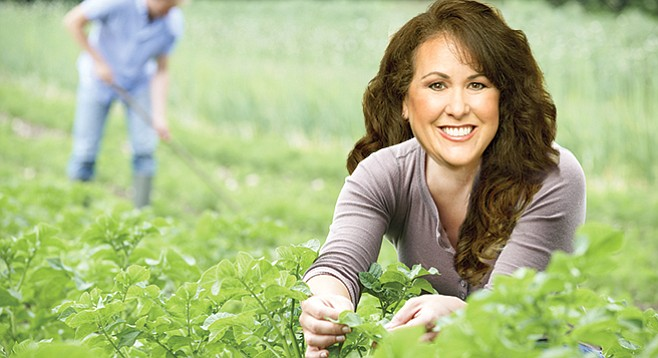 Lorena Gonzalez, depicted as happy in a field of greens (is any politician not?)