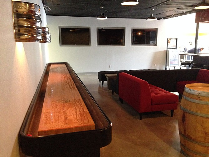 Shuffleboard, sofas, TVs, and beer-keg sconces lend to the clubhouse vibe.
