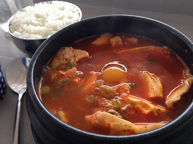 An egg cooks within a very hot sundubu jjigae, soft tofu stew