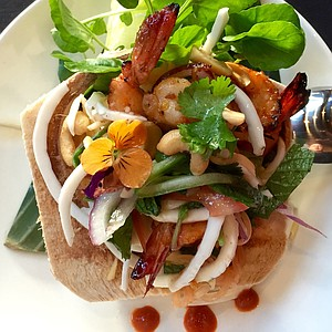 Grilled prawn salad in a coconut shell