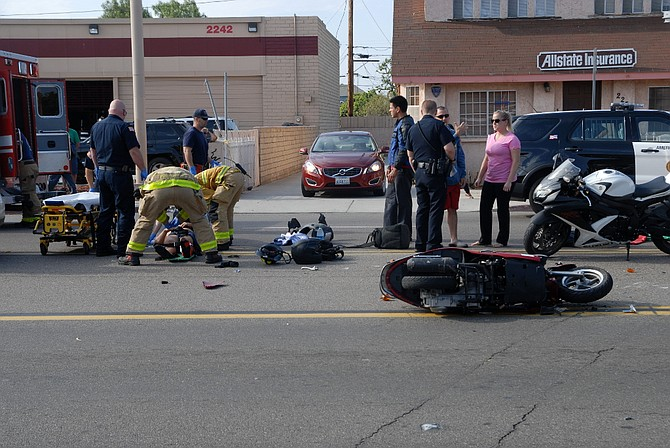 EMTs and firemen assisting the injured motorcyclist