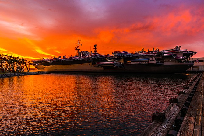 A vibrant sunset over the USS Midway during a stormy summer evening.